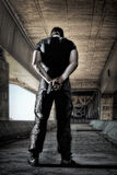 Man in black uniform and mask standing with gun. Man in headgear wearing black military uniform standing on industrial concrete background, behind view stock photo