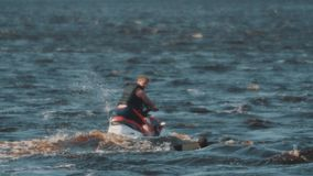 Man in black vest on a jet ski passing by surfer who floats in water of lake stock footage