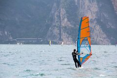Man in Black Wetsuit Standing on Orange and Blue Sailboat during Daytime Stock Images