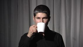 Man in black with white cup. Drinking. stock video footage