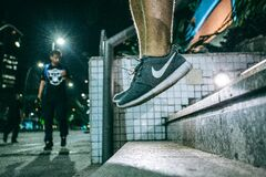 Man in Black White Nike Shoes during Nighttime Stock Photo
