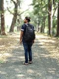 Man in Black and White T-shirt and Blue Denim Jeans Carrying Backpack stock images