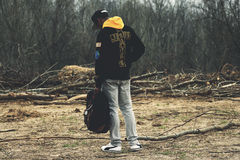 Man in Black and Yellow Hoodie and Gray Pants Holding Black Bag Standing on Dirt Ground at Daytime Royalty Free Stock Photo
