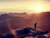 Man in black yellow jacket is taking photos by smartphone on peak in rock empires park and watching over autumn misty valley. Royalty Free Stock Image