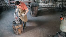 Man blacksmith in forge makes metal tools - top view stock video footage