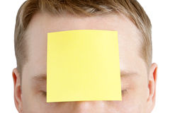 Man with a blank adhesive note on the forehead. Portrait of man with a blank adhesive note on the forehead Stock Photos