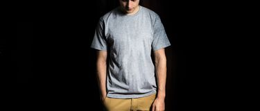Man in the blank grey, white  t-shirt, stand on a black  background, mock up Stock Photography