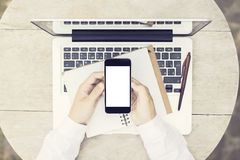 Man with blank smartphone, laptop and diary on wooden table, moc Stock Image