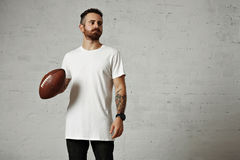 Man in blank white t-shirt with a vintage football. Tattooed and bearded model in plain white shortsleeve t-shirt holding a leather football against gray wall Royalty Free Stock Image