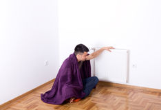 Man with blanket beside heater Royalty Free Stock Images