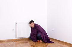 Man with blanket beside heater Royalty Free Stock Photo