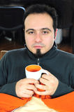 Man in blanket holding cup of tea Royalty Free Stock Photo