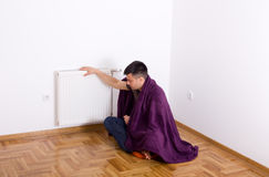 Man with blanket beside radiator Stock Images