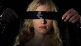 Man blindfolding woman with black ribbon, concept of blind love and submission. Stock footage stock video