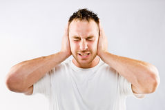 Man blocking out loud noise from ears Stock Photo