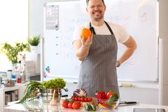 Man Blogger Holding Orange Cooking Vegetables. Portrait. Male Cook Salad at Home in Kitchen. Culinary Recipe from Tomatoes, Cucumber, Cabbage and Garlic royalty free stock photo