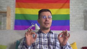 Man blogger middle-aged in the shirt on the background of the flag of the LGBT records video close up. Man blogger middle-aged in the shirt and glasses on the stock footage