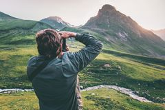Man blogger photographer taking photo of sunset mountains Travel Lifestyle hobby concept adventure active vacations Royalty Free Stock Photo