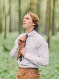 The man with blond hair and tattoo on the neck in the white shirt ties his brown tie and looking at the sky in the green. Forest. Side portrait Royalty Free Stock Image