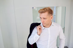 The man blonde in  white shirt with a jacket over his shoulder Stock Photography