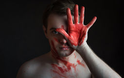 Man with blood on his face and palm Stock Images