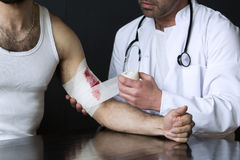 Man with bloody wound getting a bandage from doctor Stock Photo