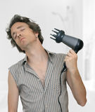 Man blow drying his hair. A man dreaming and drying his hair with a hair dryer Stock Images