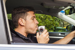 Man blowing into breathalyzer Stock Photos