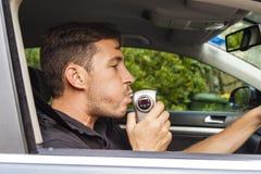 Man blowing into breathalyzer. Man in car blowing into breathalyzer Stock Photos