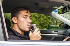 Man blowing into breathalyzer. Man in car blowing into breathalyzer Stock Image