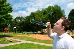 Man Blowing Bubbles. Who says your too old to blow bubbles. You can never be too old to act like a kid Royalty Free Stock Photo