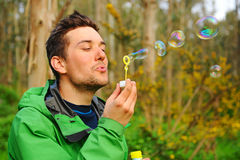 Man blowing bubbles outdoor. Young man blowing bubbles outdoor Stock Photos