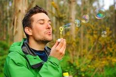 Man blowing bubbles outdoor Stock Photos