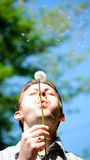 Man blowing dandelion Stock Photo
