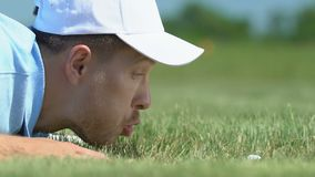 Man blowing golf ball into hole and rejoicing, breaking rules, joke, close-up. Stock footage stock footage