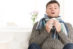 Man blowing his nose in his living room. Royalty Free Stock Photo