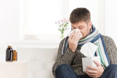 Man blowing his nose in his living room. Stock Photos