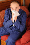 Man blowing nose. Sick middle aged man wearing pyjamas and blowing nose Stock Photo