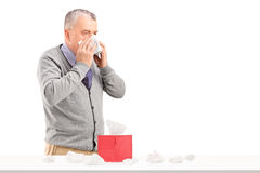 Man blowing nose with a box of tissues on a table Royalty Free Stock Photo