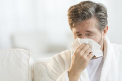 Man Blowing Nose Into Handkerchief. Mature man blowing nose into handkerchief at home Stock Images