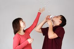 Man blowing out soap bubbles, girl catching it Stock Photo