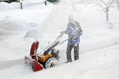 Man is blowing snow. Man is making a path by removing snow with snow blower after winter storm Royalty Free Stock Photography