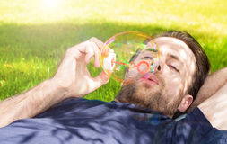 Man blowing soap bubbles while laying outdoor on grass Royalty Free Stock Photos