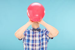 Man blowing up a balloon Royalty Free Stock Photography