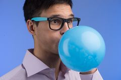 Man blowing up balloon on blue background. Royalty Free Stock Photos
