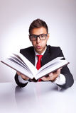 Man blowing wonders from a book. Business man blowing some imaginary wonders on top af a book he is reading Stock Photography