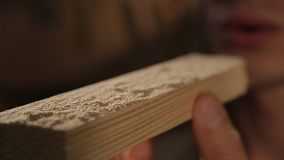 A man blows off dust from the wood element. Close stock video