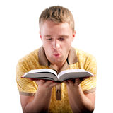 Man blows on opened book Stock Photo
