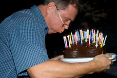 Man blows out his birthday candles royalty free stock photography