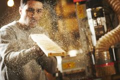 Man blows sawdust off the wood after sanding CNC router machine. Device with numerical control. Woodworking industry stock photos